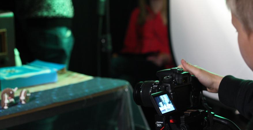 Oikeassa reunassa nuori joka kuvaa jalustalle laitetulla kameralla edessä olevalla pöydällä olevia hahmoja.