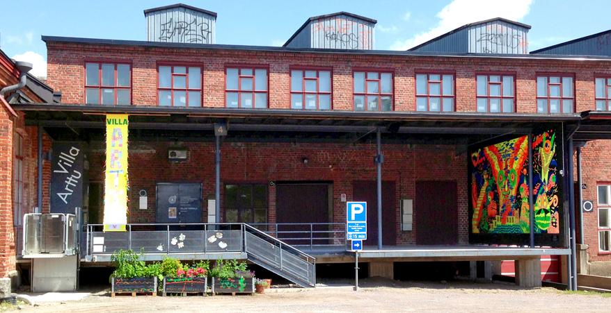 Punatiilinen Villatehtaan rakennus. Lastauslaituri jonka vasemmassa reunassa Villa Artun sisäänkäynti, oikeassa reunassa värikäs maalaus. Kaiteen edessä kolme laatikkoa joissa kasveja.