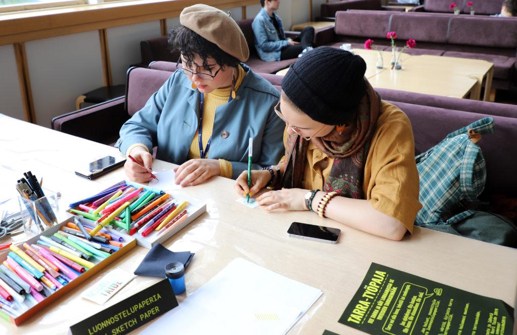 Kaksi nuorta piirtää pienille paperilapuille. Pöydällä on kyniä, papereita ja kaksi puhelinta. Taustalla sohvaryhmä jossa istuu yksi henkilö.