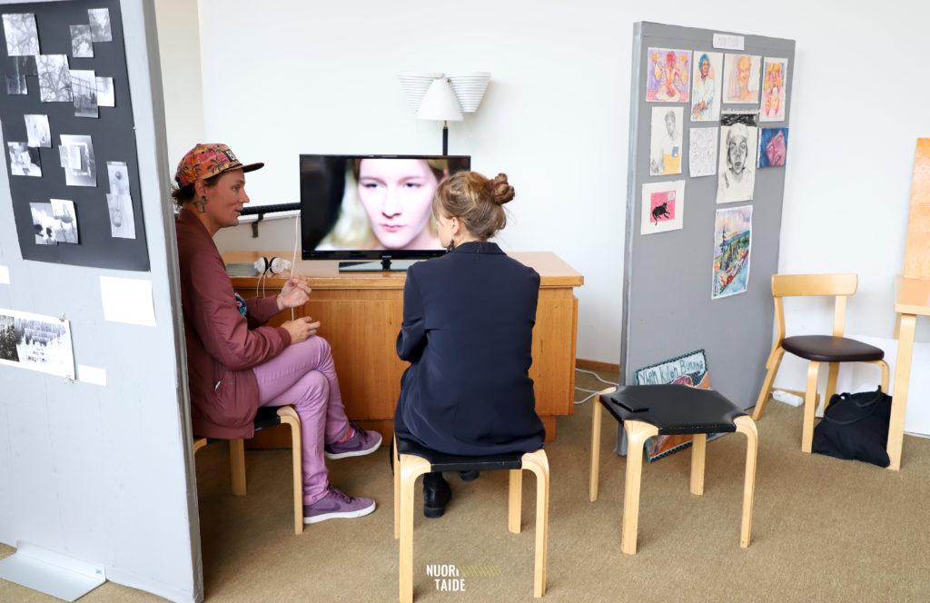 Kaksi henkilöä istumassa jakkaroilla. Katselevat tv-ruutua jossa on kuva henkilön kasvoista.