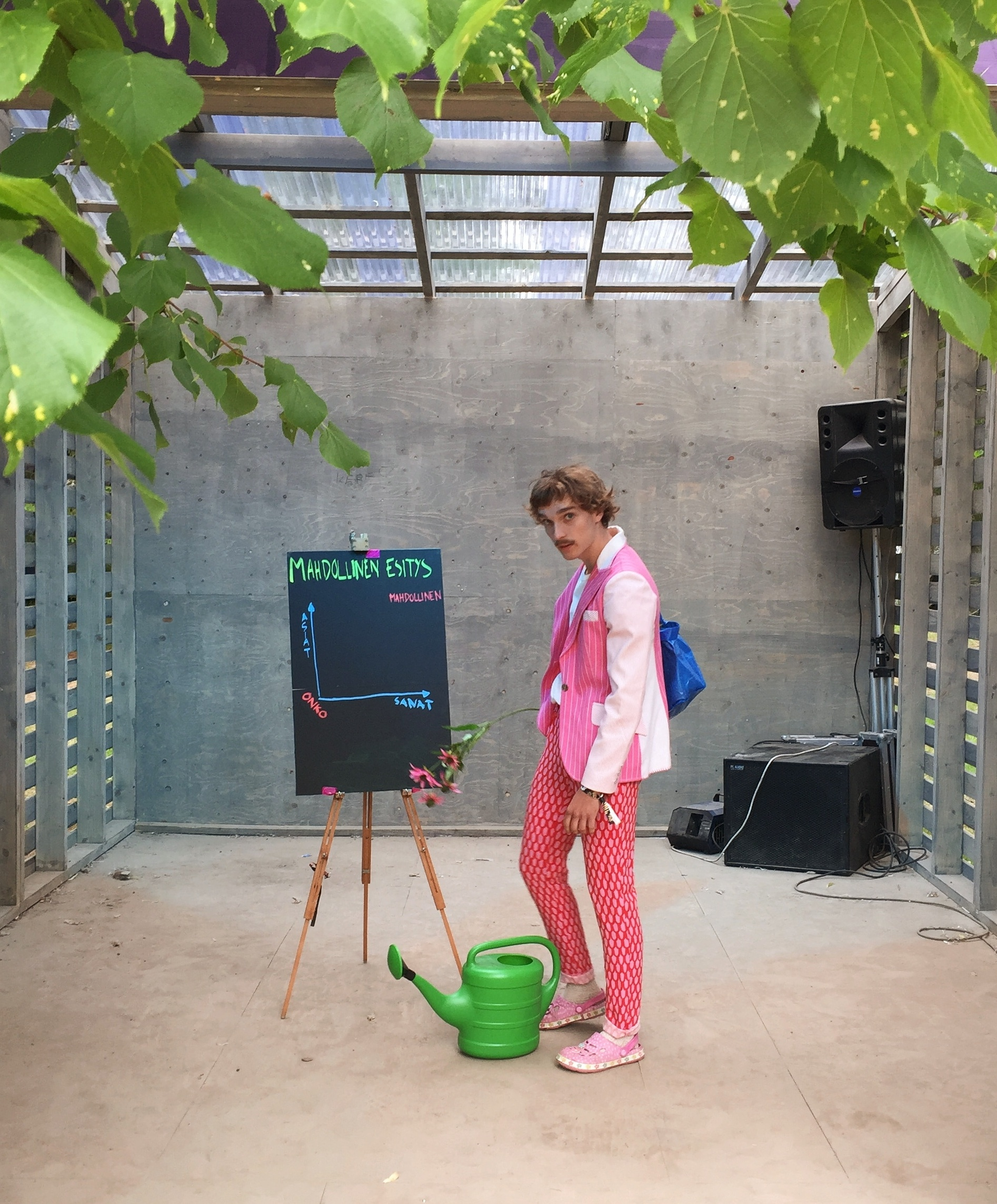 A person standing in a porch next to a watering can