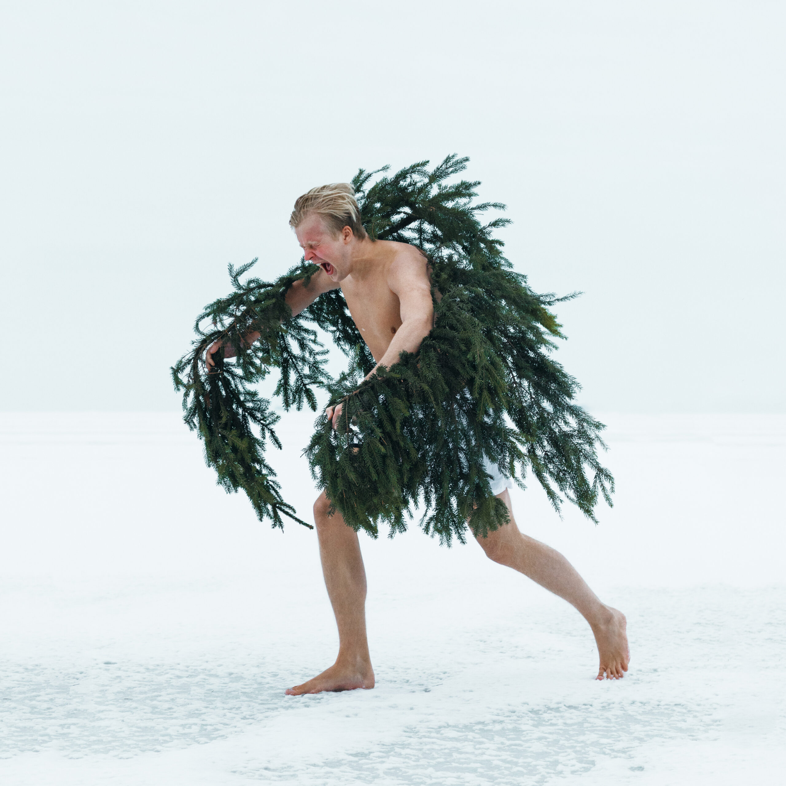 A person snding on snow and wearing pine branches