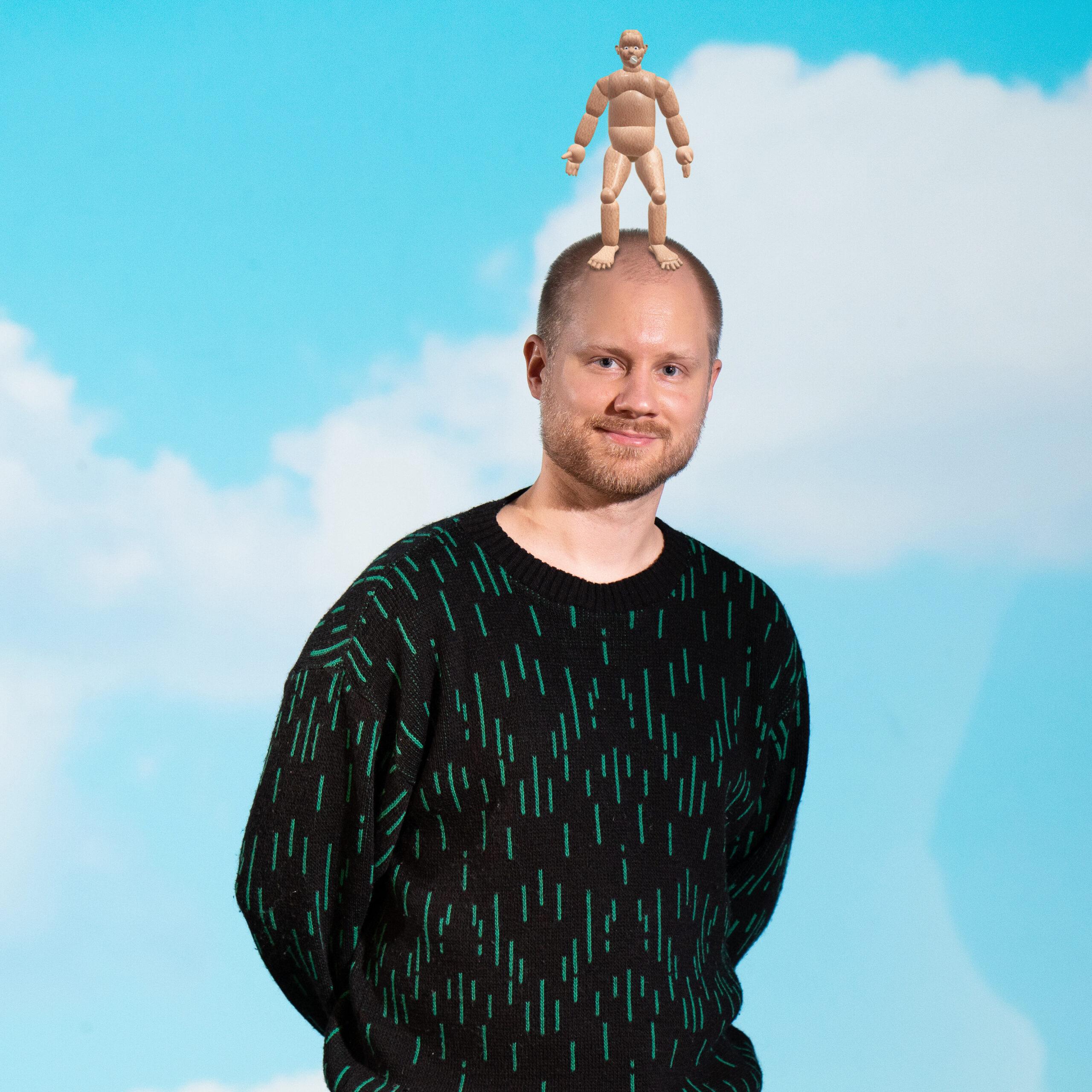 Henkilö seisoo pilivtaivaan edessä ja hänellä on pään päällä puunukke