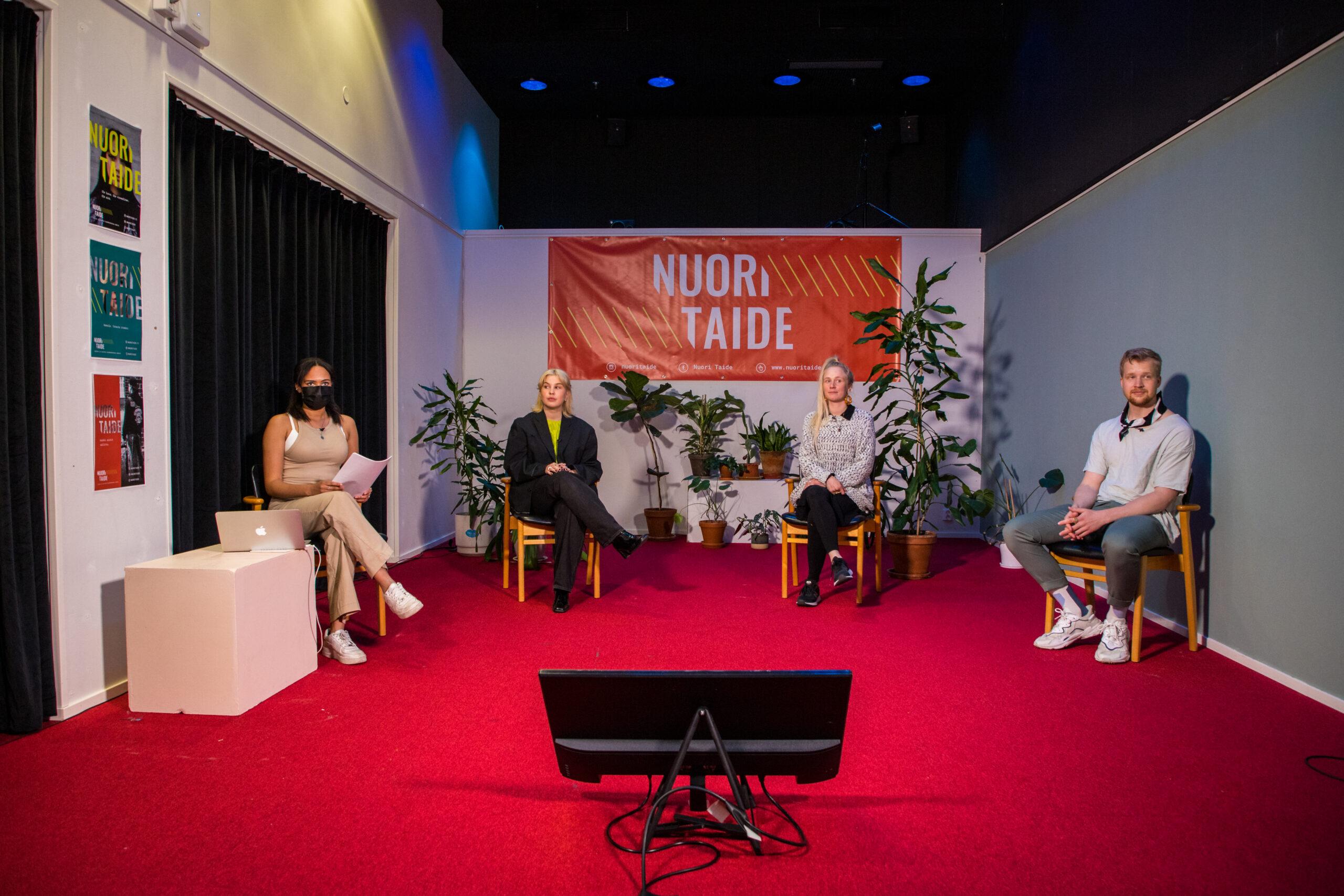 Striimaustudiosta näkymä, jossa 4 henkilö istuvat tuoteilla n. 1,5 metrin päässä toisistaan ja katsova kuvaajaan