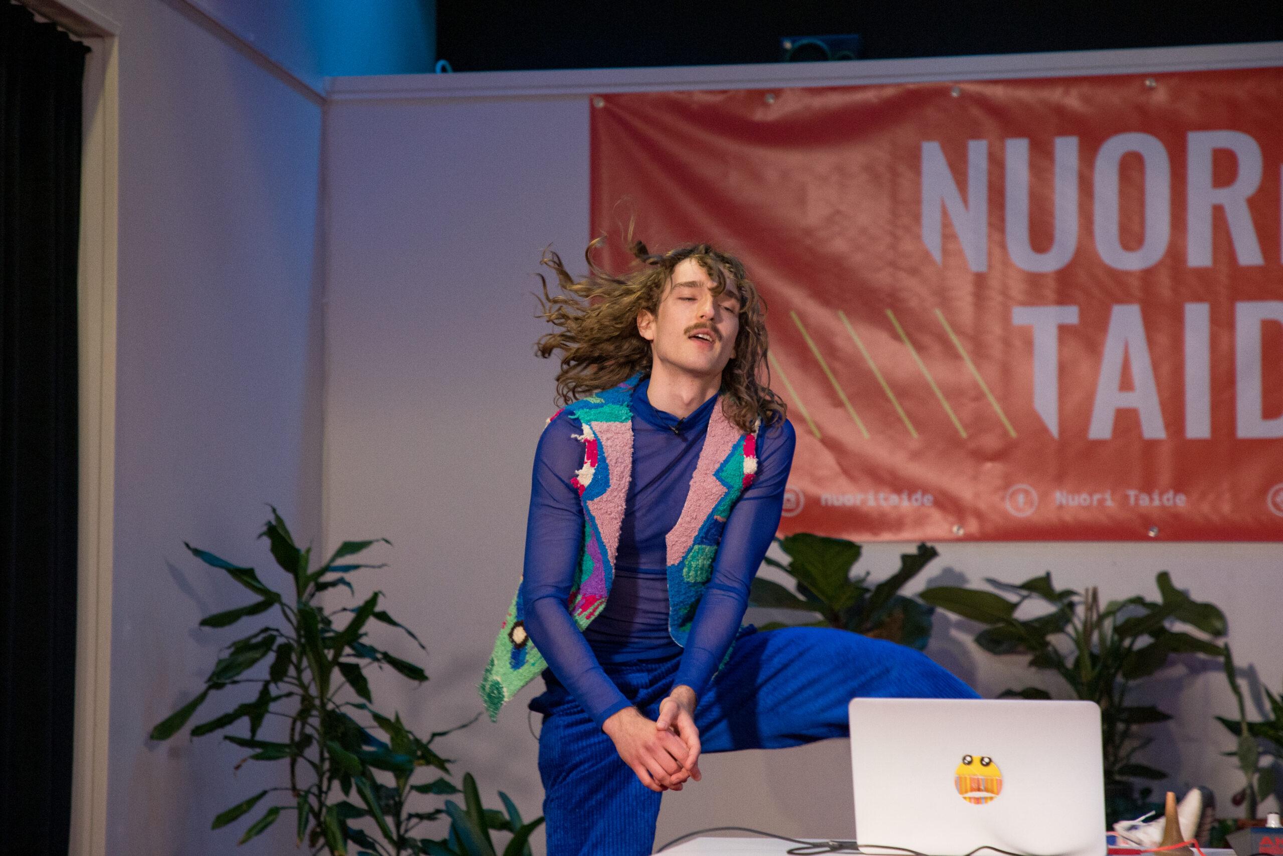 Henkilö hypähtämässä läppärin takana hiukset hulmahtaen