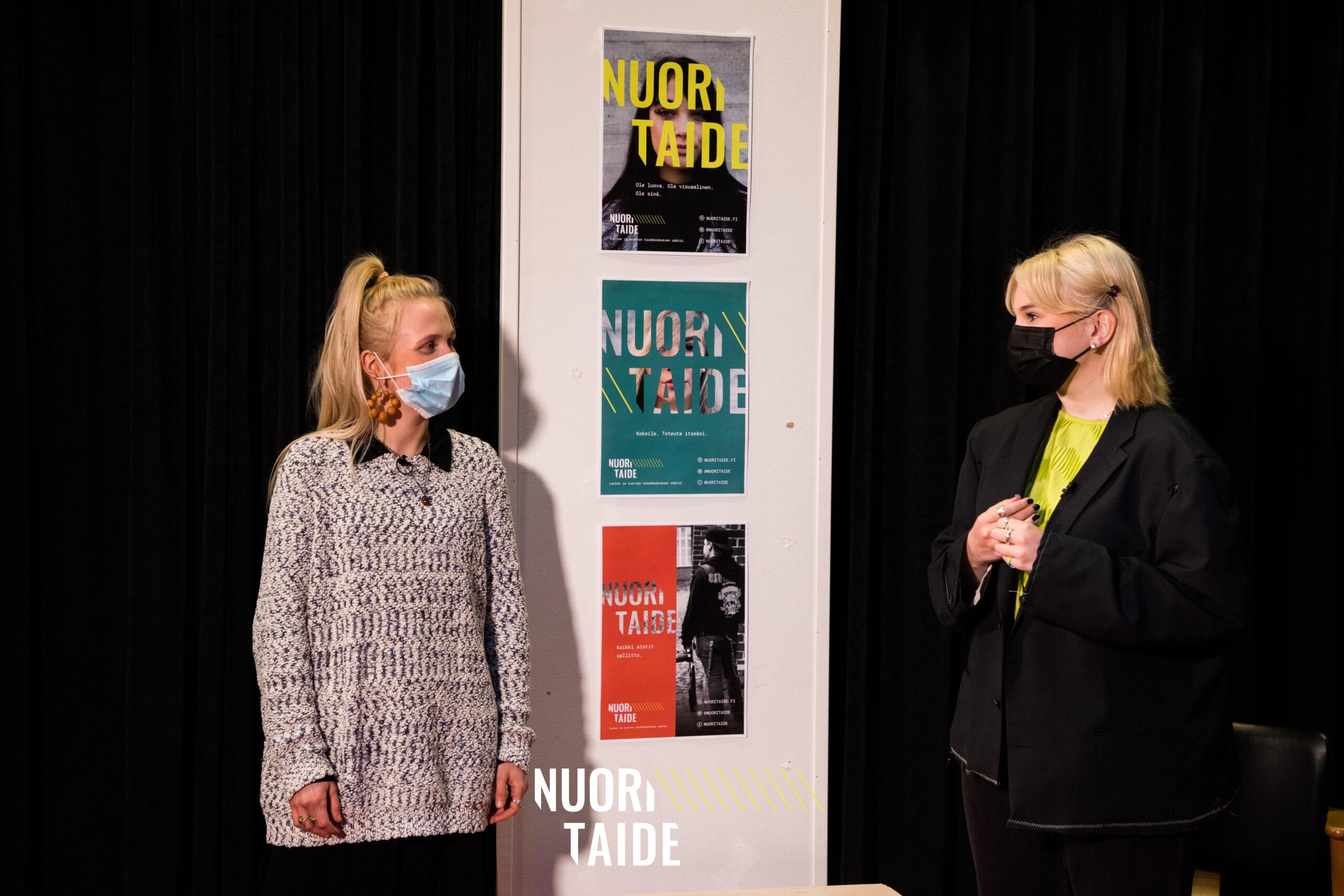 Kaksi vaalea hiuksista henkilöä seisoo ja juttelee mustaa taustaa vasten.