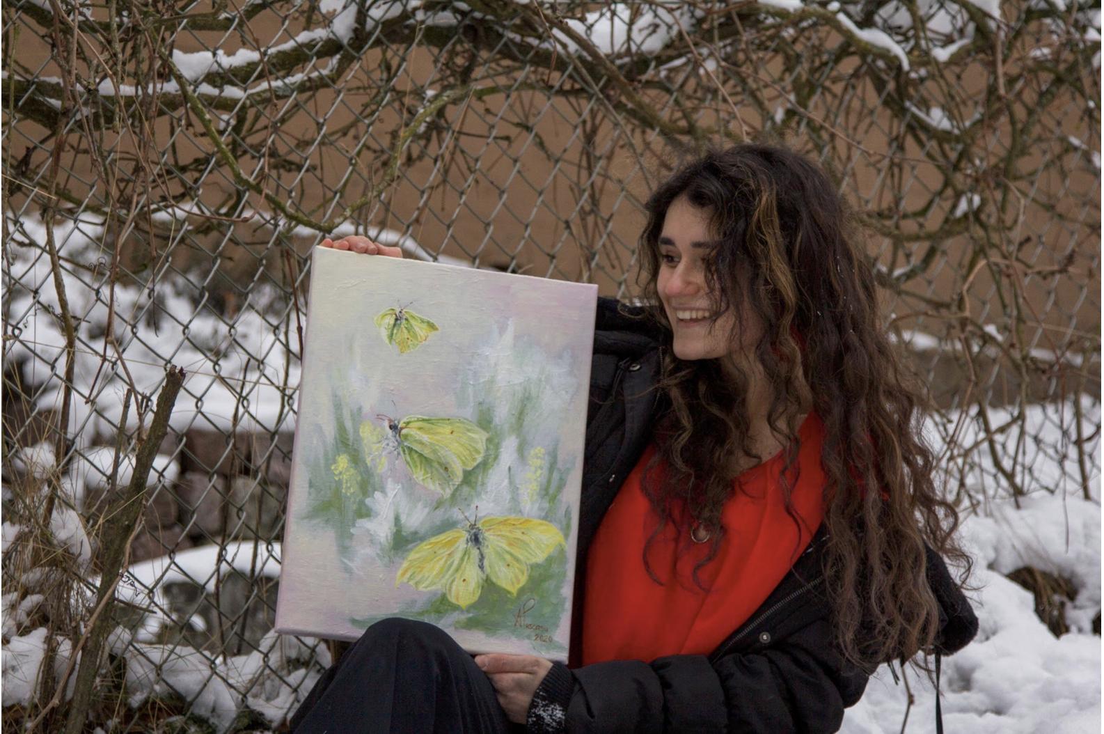 Andrea Puscasu pitää kädessään taideteosta.